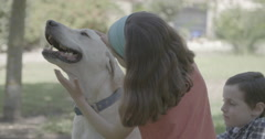 A girl and a boy petting and playing with a white dog - stock footage