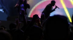 Silhouettes spectators cheerfully jumping put hands up in air on concert lumiere - stock footage