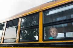 Sad child on the School Bus - stock photo