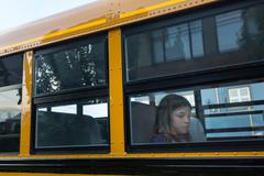 Sad girl on the School Bus - stock photo