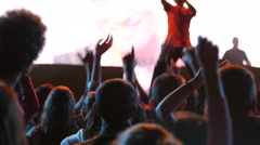 Silhouettes spectators cheerfully jumping put hands in air on concert lumiere Stock Footage