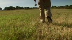 Flyfisher walking in meadow Stock Footage