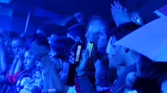 Teen crowd spectators cheerfully clapping shooting video via phone of a concert Stock Footage