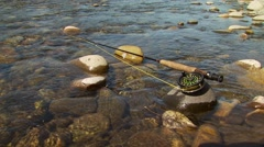 Fishing rod on rock in Gallatin River Stock Footage