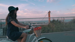 Young woman riding on old vintage bike at city center, on the bridge Stock Footage