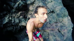 Slow Motion GOPRO POV Young Man Cliff Jump Into Ocean. Selfie Stick Stock Footage