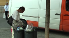 Authentic homeless man looking and eats food from the trash bin Stock Footage
