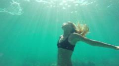 Slow Motion Woman in Bikini swimming underwater towards surface with beautifu Stock Footage