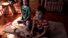 Two Twin Brothers sit in front of a television playing video games and then wres Stock Footage