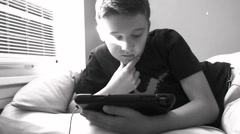 A teenage boy looks at his tablet while laying on his bed in his room Stock Footage