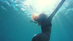 Woman in Bikini swimming underwater towards surface with beautiful sun flares - stock footage
