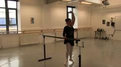 Female Ballet Dancer Using The Studio Ballet Barre for exercises Stock Footage