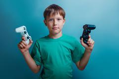 Teen  boy of twelve European appearance holds a gaming zhdoystik - stock photo