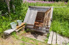 Village wooden water well with the open door and a buckets of water in the su - stock photo