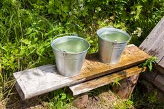 Buckets of water standing on a bench at the village water well Stock Photos
