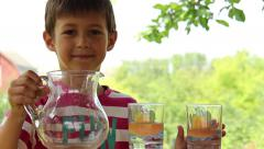 Boy pours water into a glass from a jug on the nature Stock Footage