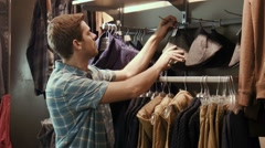 The guy tries on clothes near a mirror - stock footage