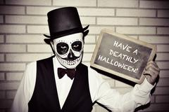 man with calaveras makeup, with chalkboard with text have a deathly halloween - stock photo