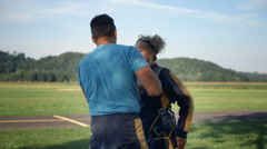 Sky diving instructor fixing the older lady's gear - stock footage