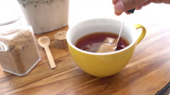 Pulling a tea bag out from a yellow cup of tea, Slow motion Stock Footage