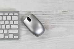 White desktop with silver wireless mouse and partial keyboard Stock Photos