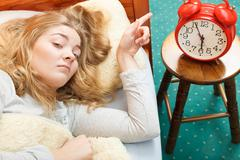 Woman waking up turning off alarm clock in morning Stock Photos