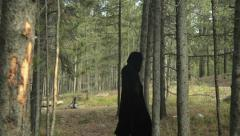Mysterious figure walking through forest devil worshipper Stock Footage