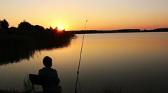 Boy fishing at dawn, the boy sitting on the beach with a fishing pole at sunrise Stock Footage
