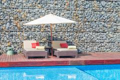 Beautiful luxury chair with umbrella deck and pool resort Stock Photos
