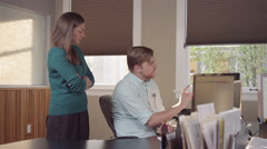 Colleages gathered around a computer in a bright office and reading charts - stock footage