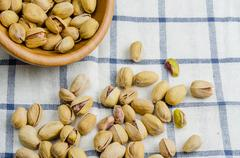 Roasted and salted pistachios on table cloth Stock Photos