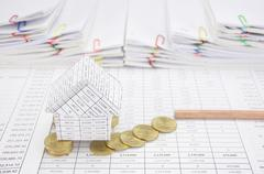 Bankruptcy of house with coins fall to ground and pencil Stock Photos