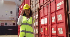 Portrait of a female dock worker standing at the harbor amidst shipping industry - stock footage