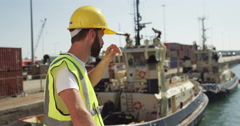 Portrait of a dock worker at the harbor amidst shipping industry activity. Stock Footage