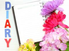 note book diary and beautiful flower bouquet background - stock photo