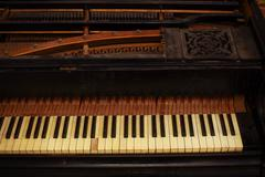 Stock Photo of black and white piano keys and wood grain with vintage sepia tone one ragged