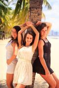 three brunette slim girls lean on palm on beach - stock photo