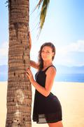 slim girl in black lace frock barefoot touches palm on beach - stock photo