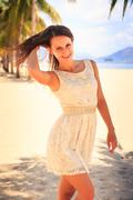 slim girl in white frock smoothes hair against row of palms - stock photo