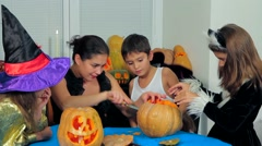 Young Woman With Children Carving Halloween Pumpkins - stock footage