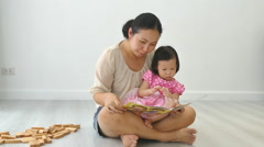mother telling a story to her baby in living room - stock footage