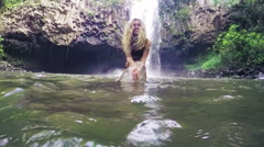 Stock Video Footage of Beautiful Young Bikini Model Splashing Water at Camera in Lush Jungle Pond in