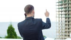 Enterprising architect talking on the phone while standing next to new building - stock footage