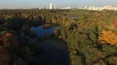 Above forest trees around small lake with on shore at autumn day Stock Footage