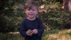 A beautiful young boy picks something up, smiles, and walks toward the camera. Stock Footage