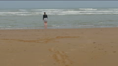 Stock Video Footage of A lady standing on the shore of Omaha Beach