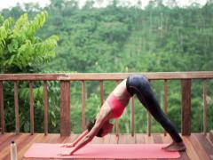 Young woman on terrace with tropical view exercising yoga, warrior pose NTSC Stock Footage