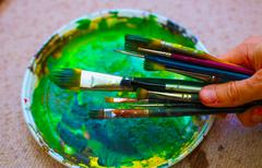 Paint brushes in man hand to the painting palette with colors - stock photo