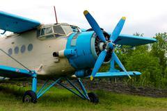 Old retro airplane on green grass - stock photo