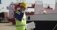 A very angry dock worker taking a call on his mobile. Shot on RED Epic. Stock Footage